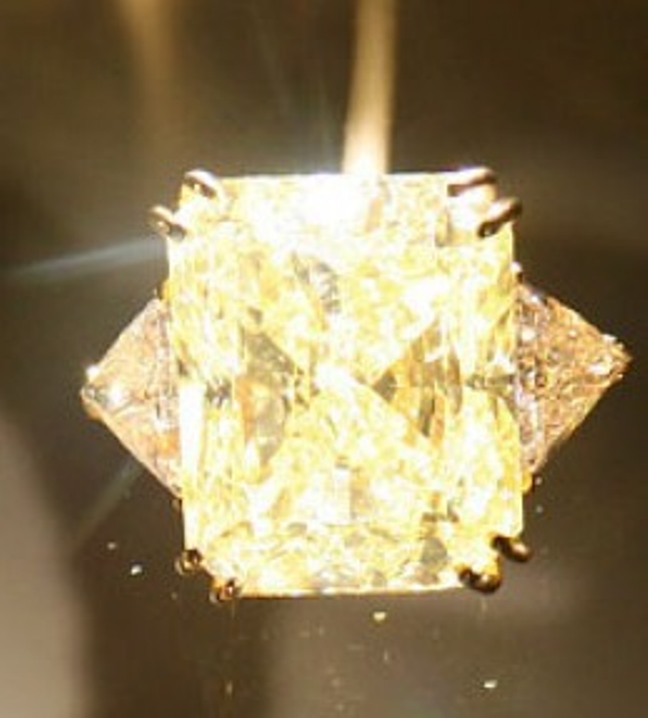 Yellow-gold ring set with a 61.12-carat, starburst-cut fancy yellow diamond flanked by triangular-cut colorless diamonds