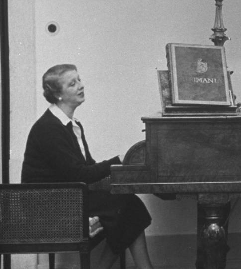 Elena Lupescu playing the piano in 1950. She seems to be wearing the same pair of pearl drop earrings