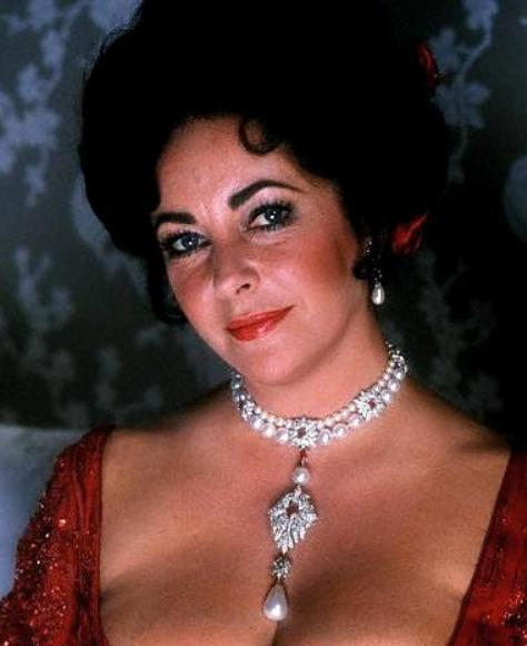 Elizabeth Taylor wearing the La Peregrina Necklace and a matching pair of pearl eardrops.
