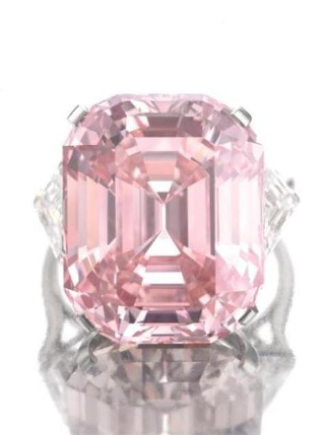 Graff Pink Diamond mounted on a ring flanked by two shield-shaped white diamonds