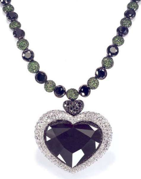 Heart-shaped Gruosi diamond set as the centerpiece of a pendant to a black and white diamond, tsavorite garnet necklace