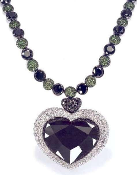 Heart-shaped Gruosi diamond set as the centerpiece of a pendant to a black and white diamond, tsavorite garnet necklace