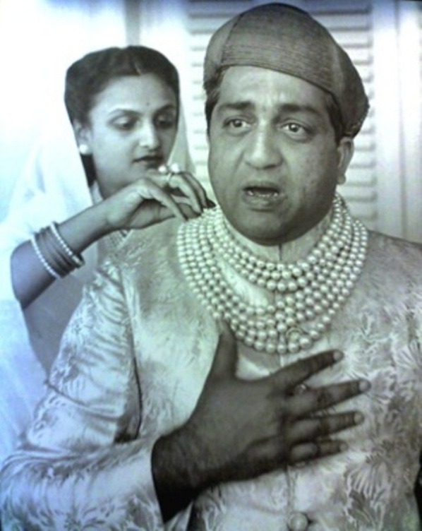 Maharajah Pratapsingh Rao Gaekwad wearing the Baroda pearl necklace. Maharani Sita Devi is in the background making adjustments to her husband's necklace