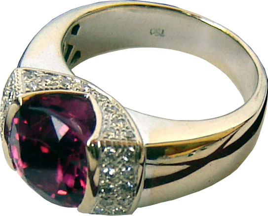 Ring with a large cushion cut rhodolite garnet in the center with diamonds on either side,set in 18k white gold.