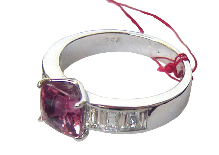 Ring with a large cushion cut Ceylon Pink Sapphire in the center with diamonds on either side