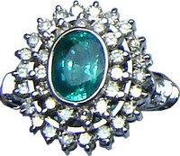 Cluster ring with a large Brazilian emerald and diamonds set in 18ct white gold.